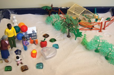 CSand tray with figures and symbolic objects, new therapies help kids with trauma