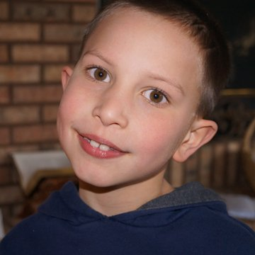 Older child smiles with hope at finding his adoptive home
