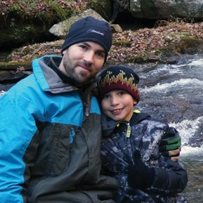 Adoptive father lovingly hugs his adoptive son